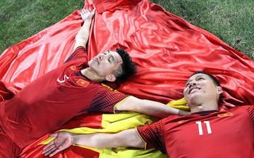 """""""Chú"""" Anh Đức nở nụ cười mãn nguyện, """"cháu"""" Văn Hậu nhắm mắt mơ màng tạo dáng pose hình với lá cờ trải trên thảm cỏ"""