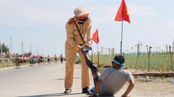 Hình ảnh CSGT gác việc, chạy tới chữa chuột rút cho runner trên đảo Lý Sơn gây ấn tượng - Ảnh 1.