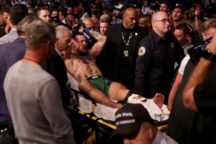 Võ sĩ MMA nổi tiếng nhất thế giới Conor McGregor gãy gập chân kinh hoàng tại UFC, cay đắng rời nhà thi đấu trên cáng - Ảnh 6.