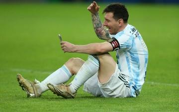 Messi ngồi bệt xuống sân, gọi video khoe huy chương với vợ con
